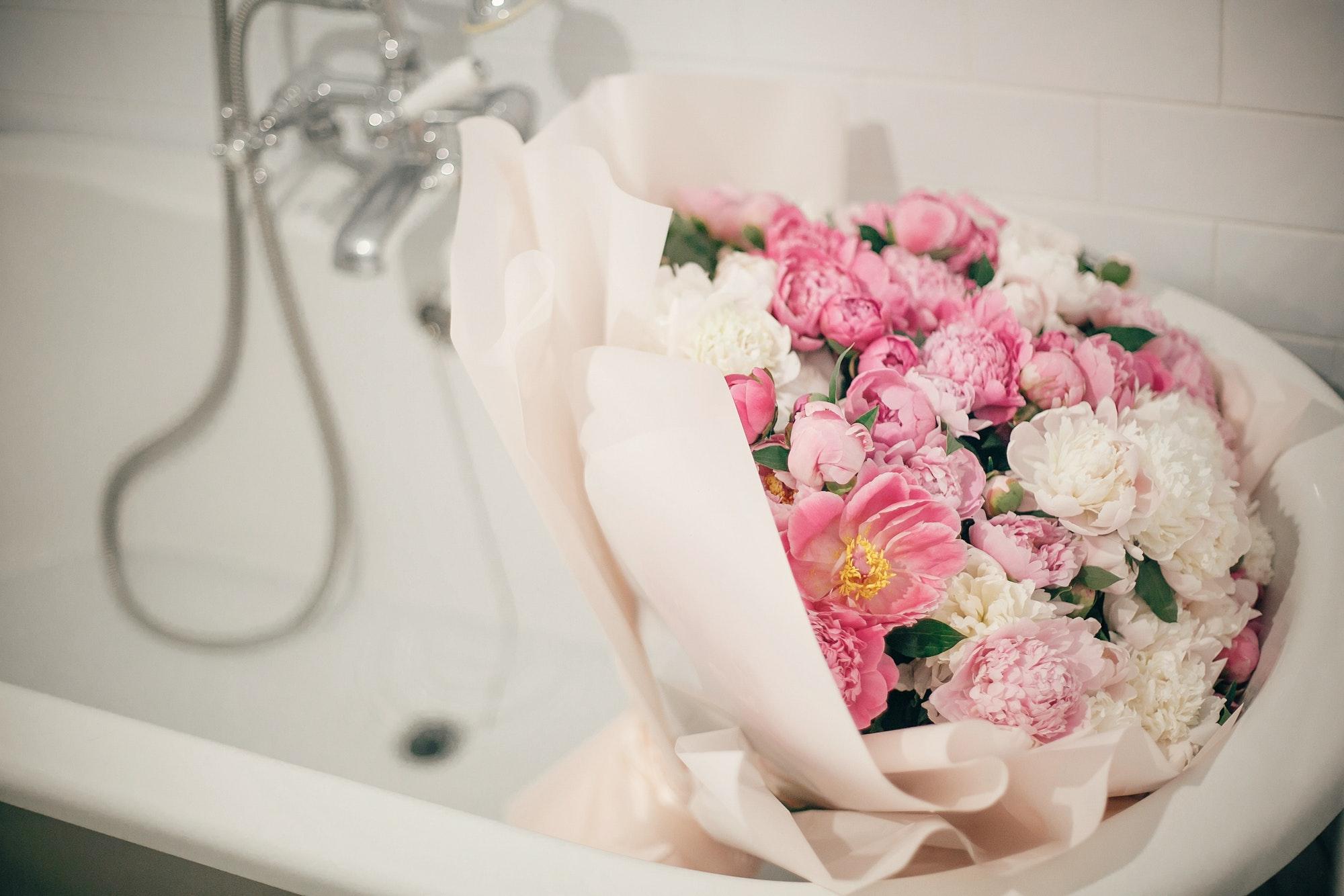 Big stylish peony bouquet in bathtub